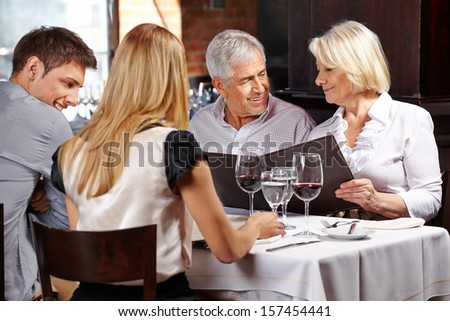 Family with two senior people in restaurant holding the menu - stock photo