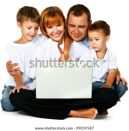 Family with two sons sitting on floor and using laptop computer - stock photo