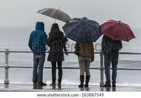 Family with umbrella waterfront