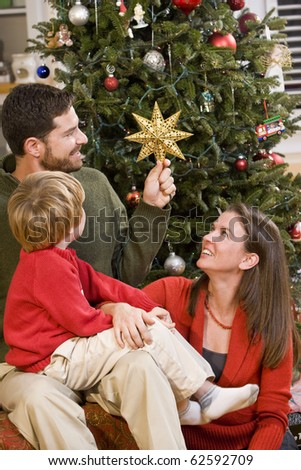 Family with 4 year old boy sitting by Christmas tree, dad holding star - stock photo