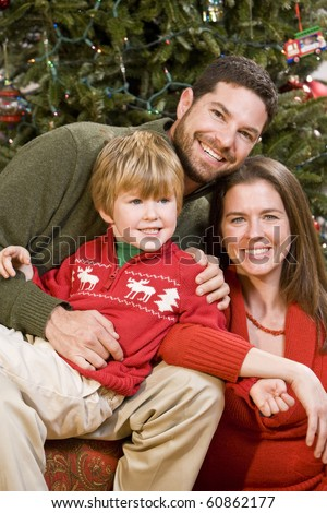 Family with 4 year old boy sitting in front of Christmas tree - stock photo