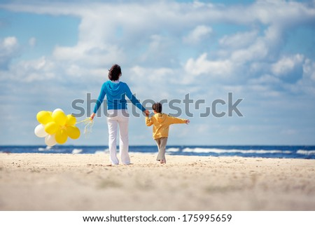 Family with yellow balloons on the beach - stock photo