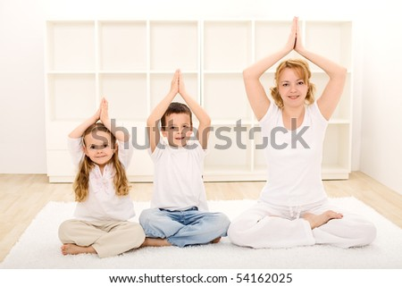 Family - woman and kids - doing yoga exercises indoors