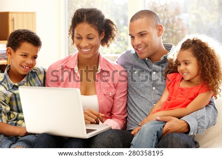 Family working on laptop at home - stock photo