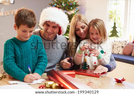 Family Wrapping Christmas Gifts At Home - stock photo
