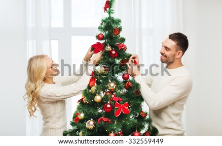 family, x-mas, winter holidays and people concept - happy couple decorating christmas tree at home - stock photo