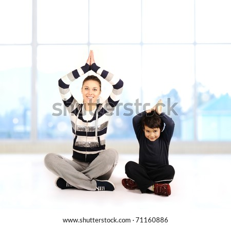 Family - young woman and kid - doing yoga exercises indoors - stock photo