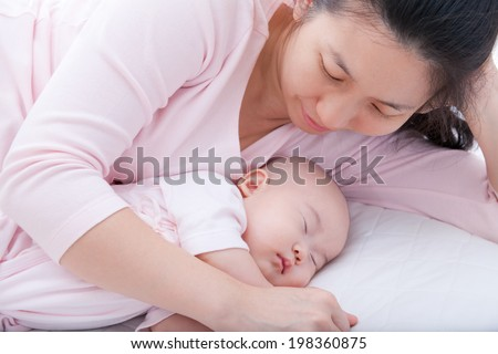 Family. Young woman embrace her daughter sleeping in the bed. Mother day concept - stock photo