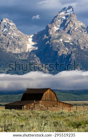 Famous barn in Mormon Row Historic District with Grand Tetons and a fog bank in distance - stock photo