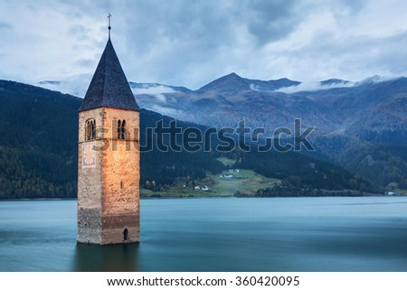Famous Bell Tower of the Sunken church in Resia Lake, Italy. - stock photo