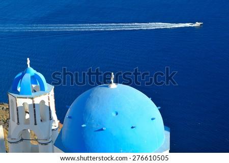 Famous blue dome churches of Ag. Spyridonas and Ag. Anastasis in Oia, Santorini, Greece - stock photo