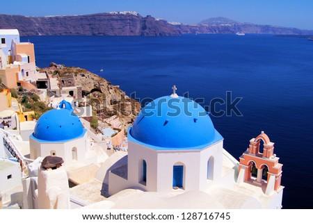 Famous blue dome churches of Santorini, Greece overlooking the scenic caldera - stock photo