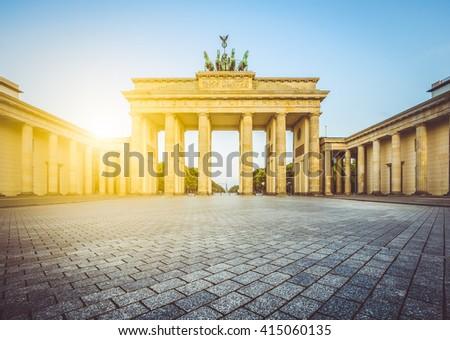 Famous Brandenburger Tor (Brandenburg Gate), a major landmark and national symbol, in golden morning light at sunrise with retro vintage Instagram style pastel toned filter effect, Berlin, Germany - stock photo