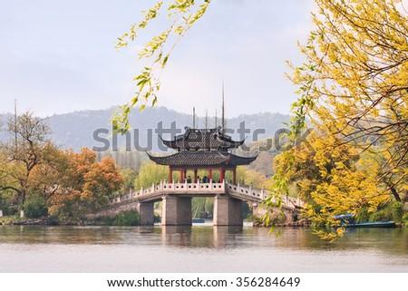 Famous bridge at enchanting West Lake in autumn colors, Hangzhou, China - stock photo