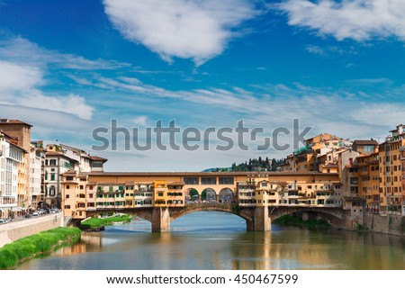 famous bridge Ponte Vecchio over waters of river Arno with cloudy sky, Florence, Italy - stock photo