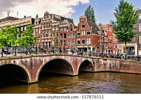 Famous canal houses of Amsterdam with bridge  - stock photo