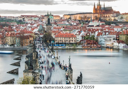 Famous Charles Bridge (Karluv most) over Vltava river with walking tourists, Prague Castle and St. Vitus cathedral in twilight evening light, Prague, Czech Republic - UNESCO world heritage site - stock photo