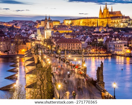 Famous Charles Bridge (Karluv most) over Vltava river with walking tourists, Prague Castle and St. Vitus cathedral at golden evening light, Prague, Czech Republic - UNESCO world heritage site - stock photo