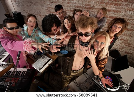 Famous DJ crowded by fans and requests at a party - stock photo