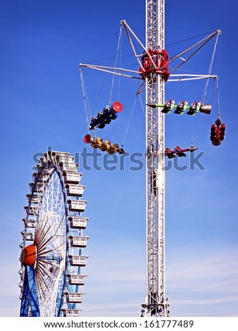 famous ferris wheel and a fairground ride at the oktoberfest in munich - germany - stock photo