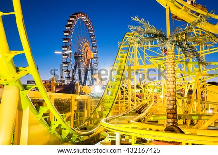 famous ferris wheel and rollercoaster at the oktoberfest in munich - germany