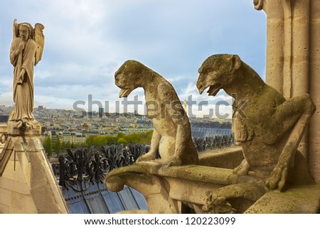 Famous figures of gargoyles and angel of Notre Dame (built in 1240) over Paris aerial - stock photo