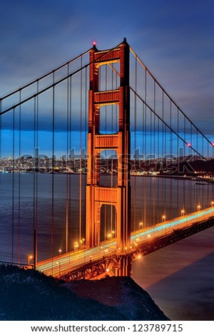 famous Golden Gate Bridge and San Francisco lights at sunset - stock photo