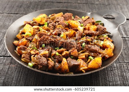 Famous Indian fried tender mutton or lamb served in a iron cookware,