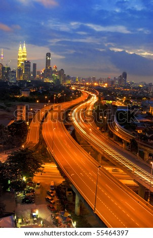 famous landmark of kuala lumpur with fast moving vehicle on highway - stock photo