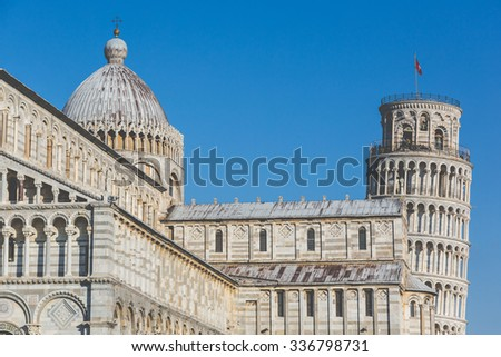 Famous leaning tower and Cathedral in Pisa, Italy. Close up view of these two famous Italian buildings, with a blue sky on background. Travel and architecture concepts. Vintage edit. - stock photo
