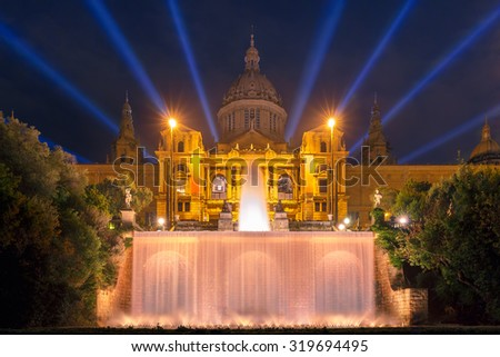 Famous light show and magic fountains in front of the National Art Museum at Placa Espanya in Barcelona at night, Catalonia, Spain - stock photo
