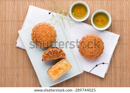 Famous moon cake with assorted nuts and egg yolk. Mooncake and tea,Chinese mid autumn festival food. - stock photo