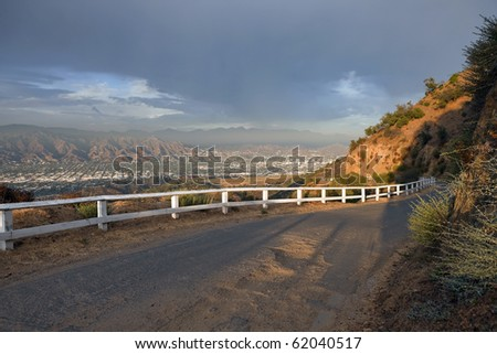 Famous Mulholland Hwy with thunder clouds and afternoon light.  High in the hills above Los Angeles Burbank and Glendale, California. - stock photo