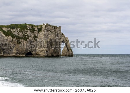 "Famous natural cliffs ""Porte d'Aval"" in Etretat. Etretat is a commune in Seine-Maritime department in Haute-Normandie region in France. Etretat is now a famous French seaside resort. - stock photo"