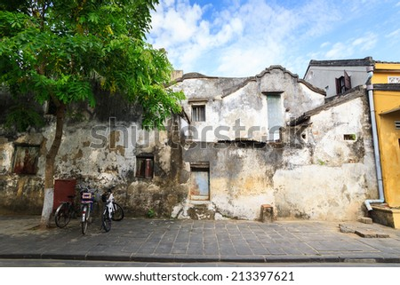 Famous old wall at Hoi An Ancient Town in early morning sunshine, Quang Nam, Vietnam. Hoi An is recognized as a World Heritage Site by UNESCO. - stock photo