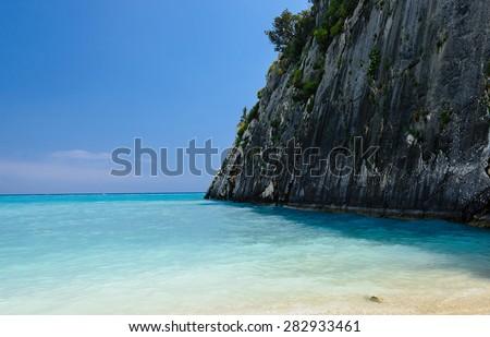 Famous paradise beach Xygia Sulfur. Blue lagoon wide angle view of rocky coast, tide, blue sky and white sand at Zakynthos island, Greece - stock photo