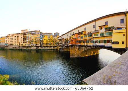 Famous Ponte Vecchio bridge over river Arno in Florence - stock photo