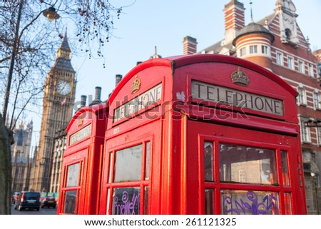 Famous red telephone box with Big Ben on background in a sunny early morningin London. There are also some chimneys and trees. - stock photo