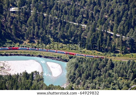 famous red train Glacier Express drives alongside river Rhine in canyon - stock photo