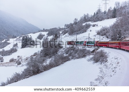 Famous sightseeing train Glacier Express  running in the swiss alps in winter  Switzerland. - stock photo
