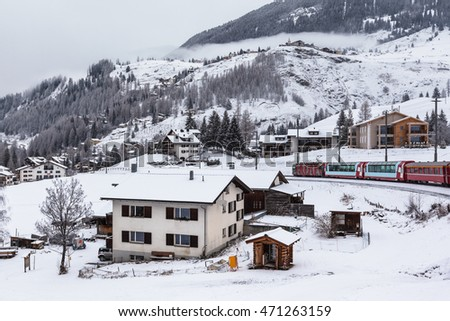 Famous sightseeing train Glacier Express  running in the swiss alps through a village in winter  Switzerland.