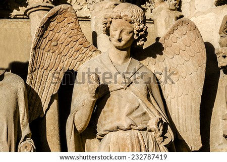 Famous smiling angel on Notre-Dame de Reims cathedral facade (Our Lady of Reims, 1275), Reims, France. Reims Cathedral is seat of the Archdiocese of Reims, where kings of France were crowned. - stock photo
