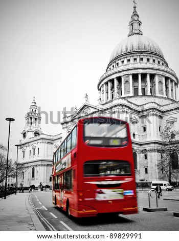 Famous St. Paul's Cathedral with iconic red bus in London speeding past - stock photo