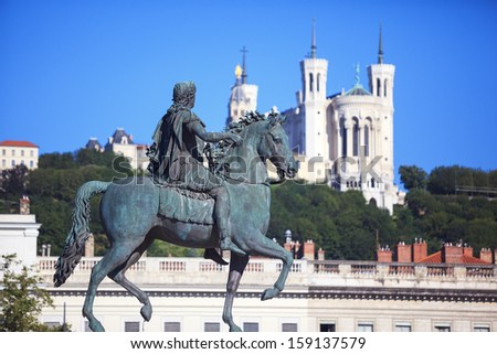 Famous statue of Louis XIV and Basilique of Notre Dame de Fourviere on a background  - stock photo