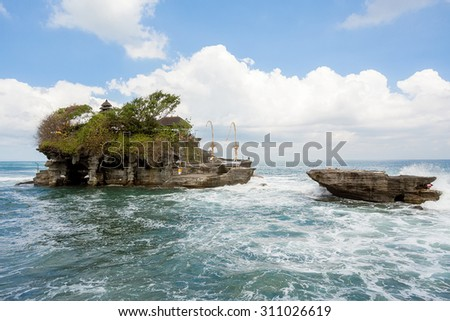 famous Tanah Lot Temple on Sea in Bali Island Indonesia with blue sky and waves