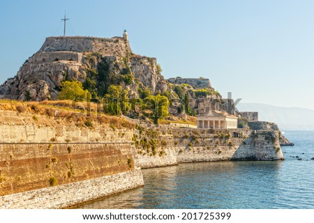 Famous touristic landmark old venetian fortress with walls going to sea and clock tower in the morning, located at Kerkyra city, Corfu, Greece - stock photo