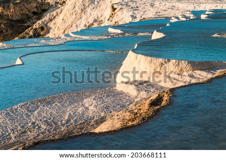 Famous travertine pools and terraces in Pamukkale, Turkey at sunset - stock photo