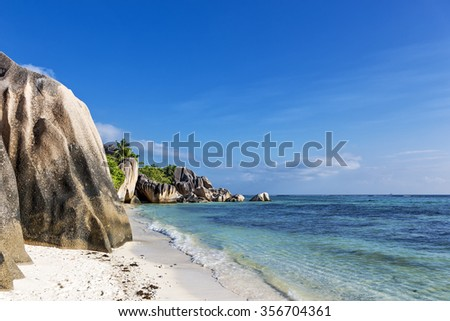 Famous tropical sandy beach Anse Source d'Argent on Seychelles islands. Sunny day, blue sky, green palm trees and turquoise ocean
