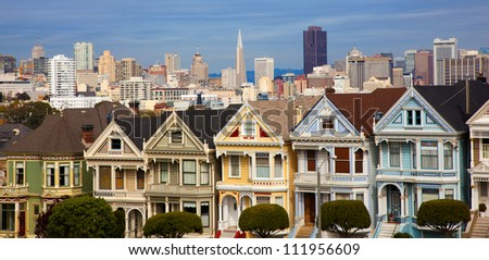 Famous Victorian row houses in San Francisco with skyline.  Houses referred to as the painted ladies - stock photo