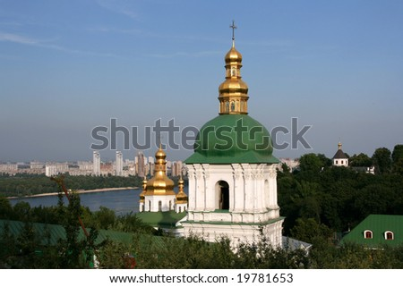 Famous view of Kiev Pecherska Lavra with modern districts and skyscrapers in the background. Ukrainian capital city. - stock photo